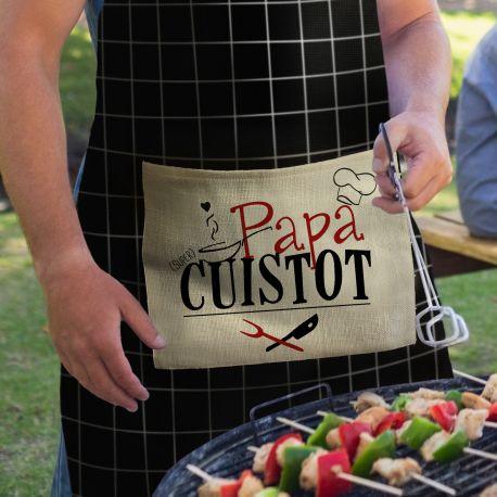 Ce tablier de cuisine en tissu toucher coton naturel à carreaux noirs est doté d'une poche imprimée en tissu à l'aspect lin écru et doux...