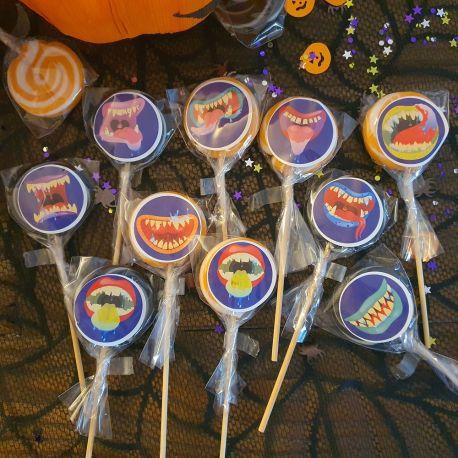 Assortiment de 10 sucettes foraines orange et noires à l'effigie de décors de bouches de monstres d'Halloween, idéal pour la...